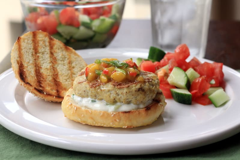 Indian Chicken Burger and tomato salad on a white plate