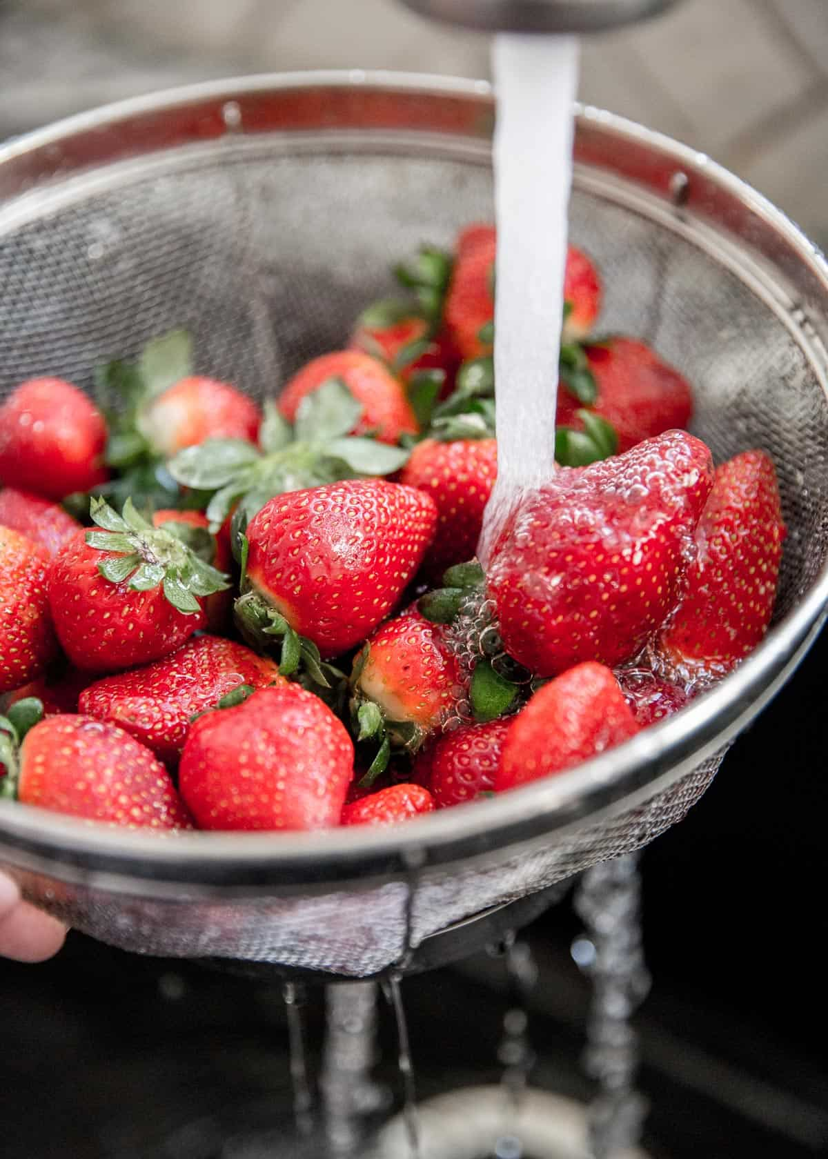 rinsing strawberries in a strainer
