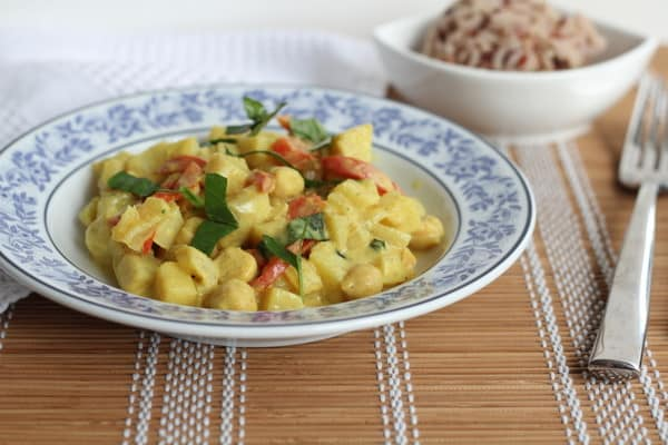 Potato Curry with Mango and Basil in a blue and white bowl
