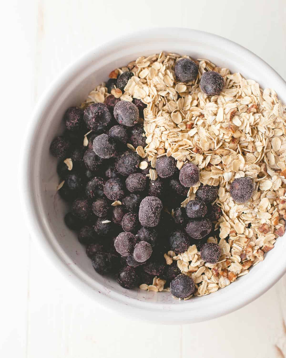 ingredients for blueberry oatmeal in a white bowl