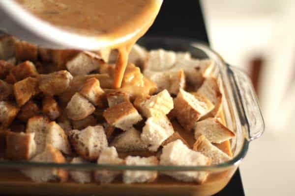 pouring pumpkin mix over bread cubes in a baking dish