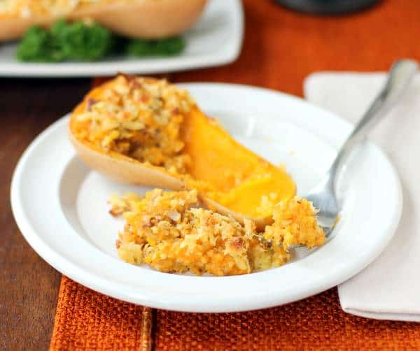 a baked squash and a fork on a white plate