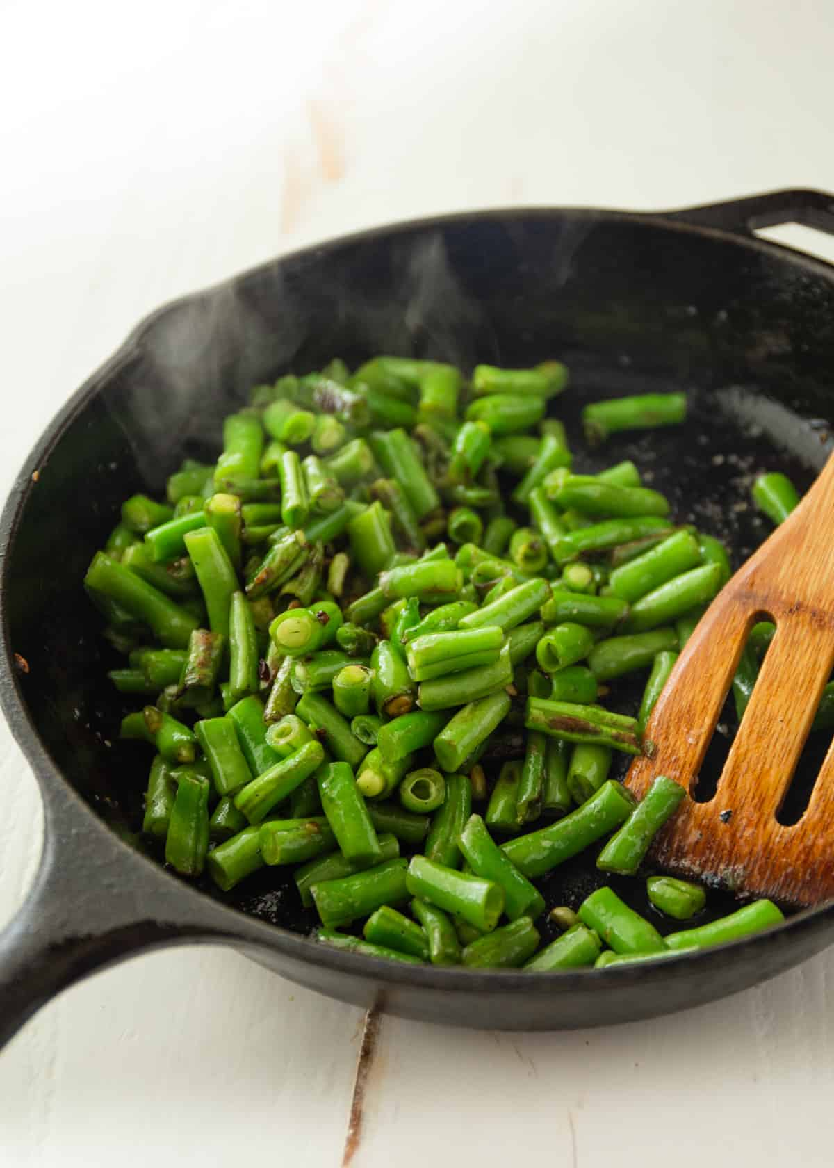 dry fried green beans in a cast iron skillet