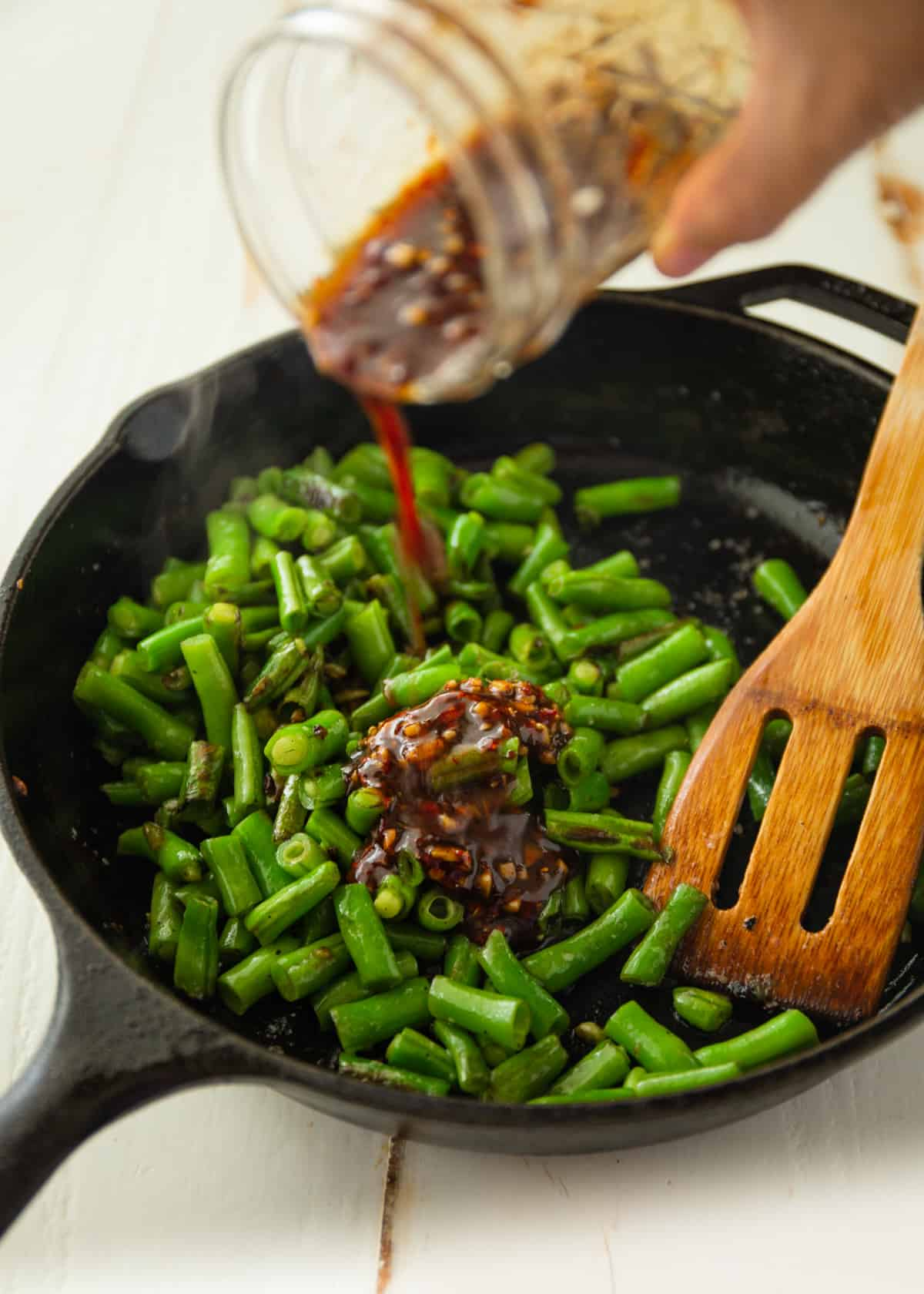 adding sauce to green beans in a cast iron skillet