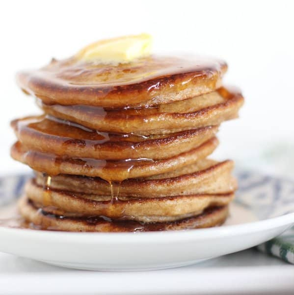 a stack of pancakes topped with butter and syrup on a blue and white plate