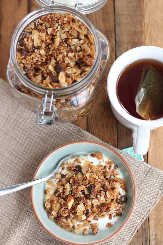 granola in a glass jar, and topping yogurt in a blue bowl
