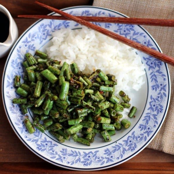 spicy green beans and rice on a blue and white plate