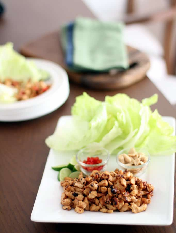 lettuce, chicken and toppings on a white cutting board