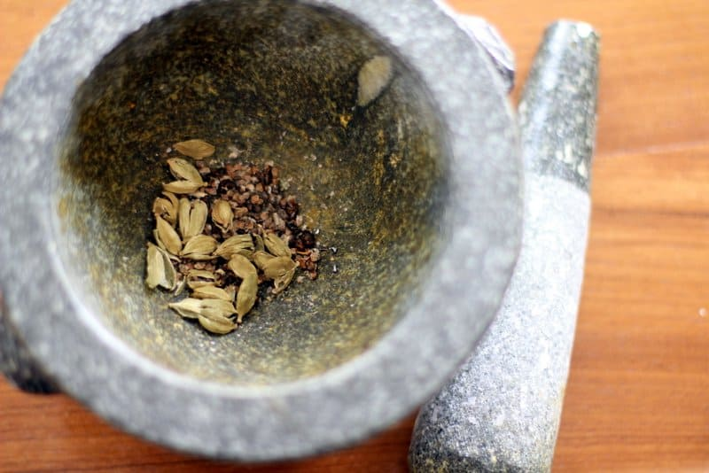 Whole Cardamom with a mortar and pestle