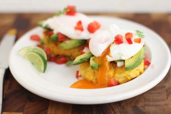 poached eggs on top of corn cakes on a white plate