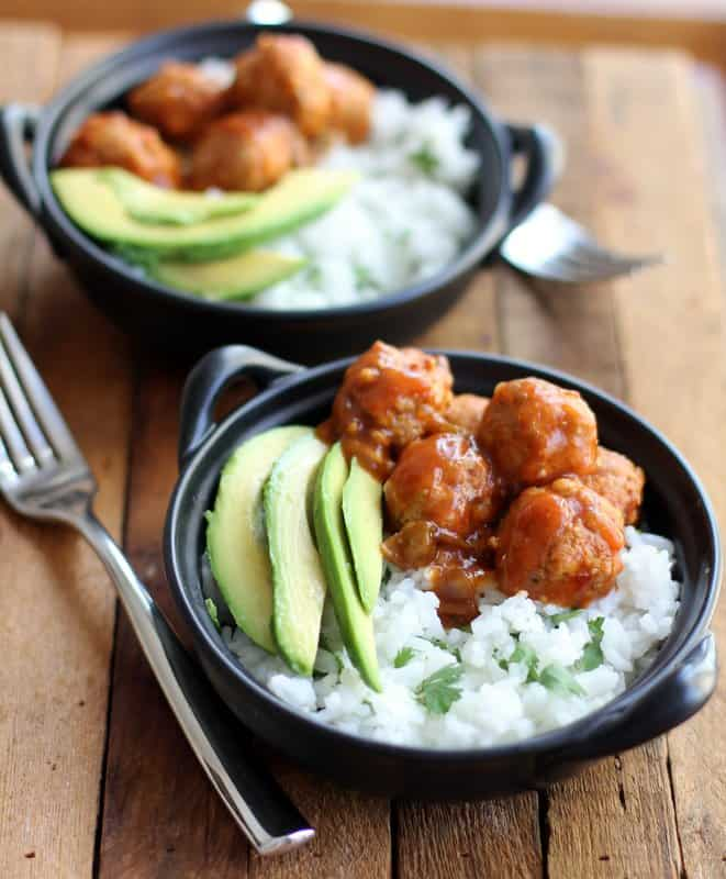 meatballs, rice and avocado slices in a black bowls