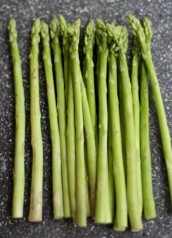stalks of asparagus on a grey countertop