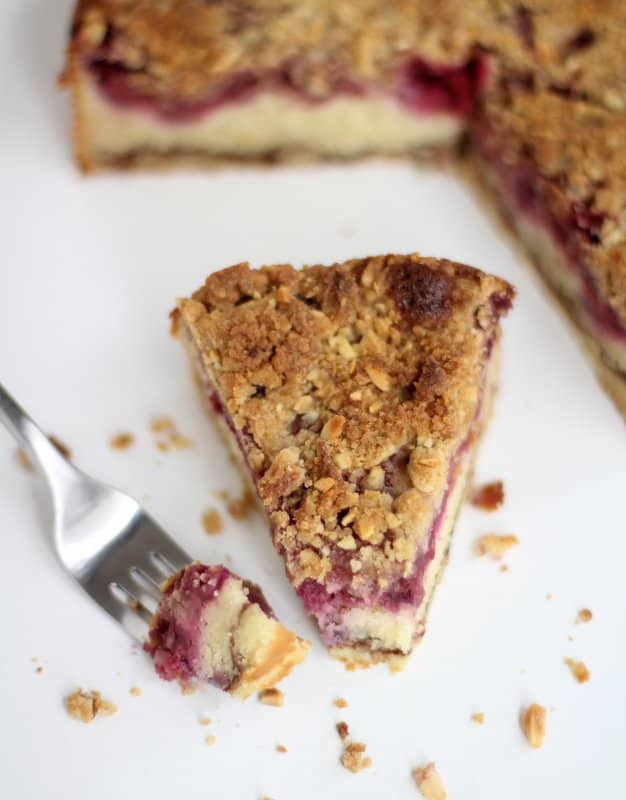 a fork and a slice of raspberry cake on a white countertop