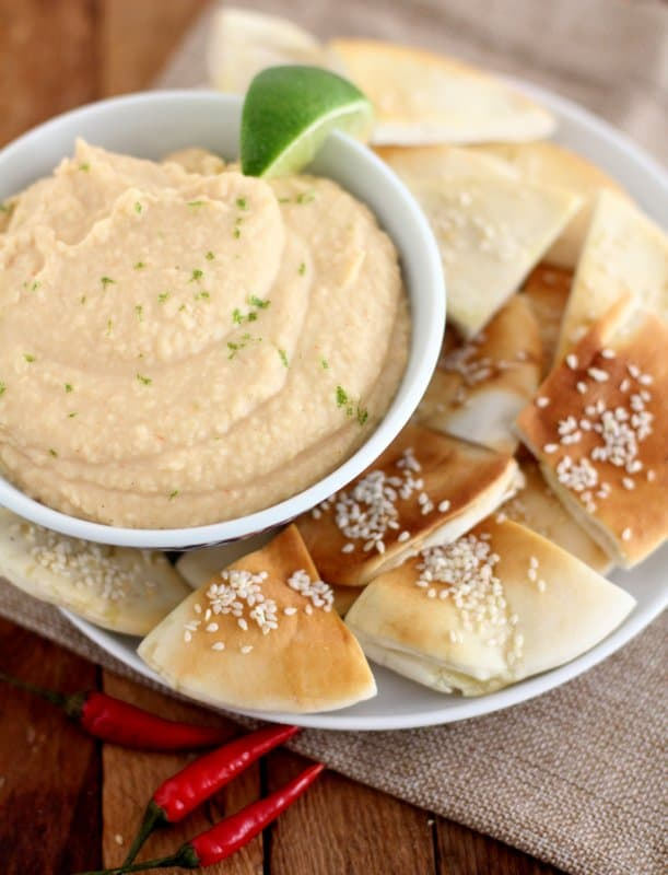 white bean dip in a white bowl with sesame pita chips on a white plate