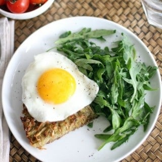 hash browns with a fried egg and arugula on a white plate