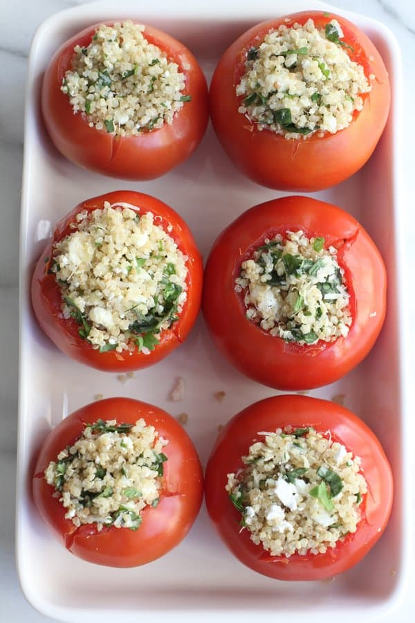 quinoa stuffed tomatoes in a white baking dish