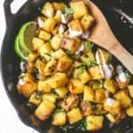 stirring aloo bahji in a cast iron skillet