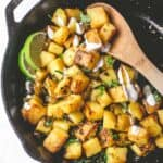 stirring aloo bahji in a cast iron skillet