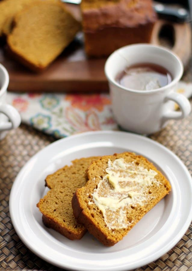 slices of pumpkin cider bread with butter on a white plate next to a cup of tea
