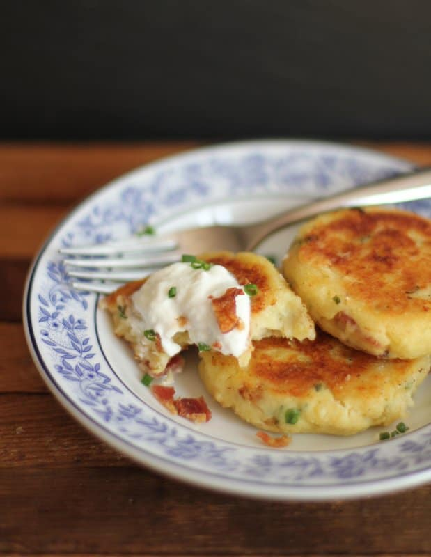 potato cakes on a blue and white plate with a fork