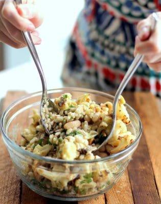 stirring cauliflower salad in a glass bowl