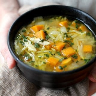 chicken, butternut squash and orzo soup in a black bowl