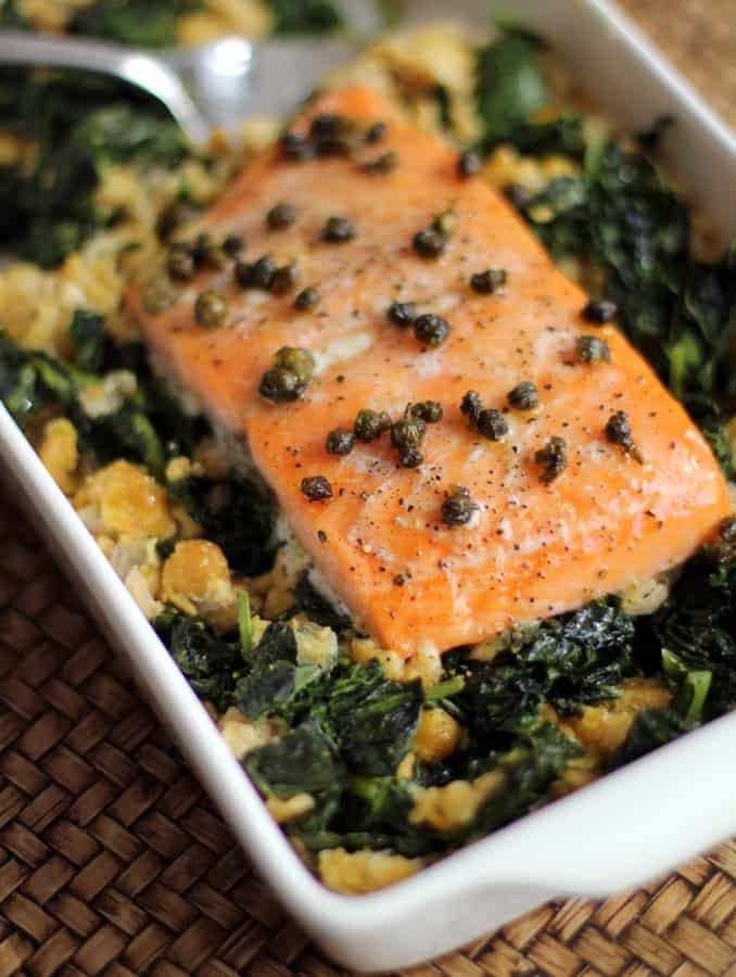 salmon and greens in a white baking dish