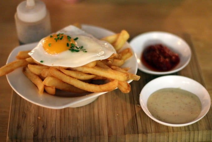 a plate of french fries topped with a fried egg
