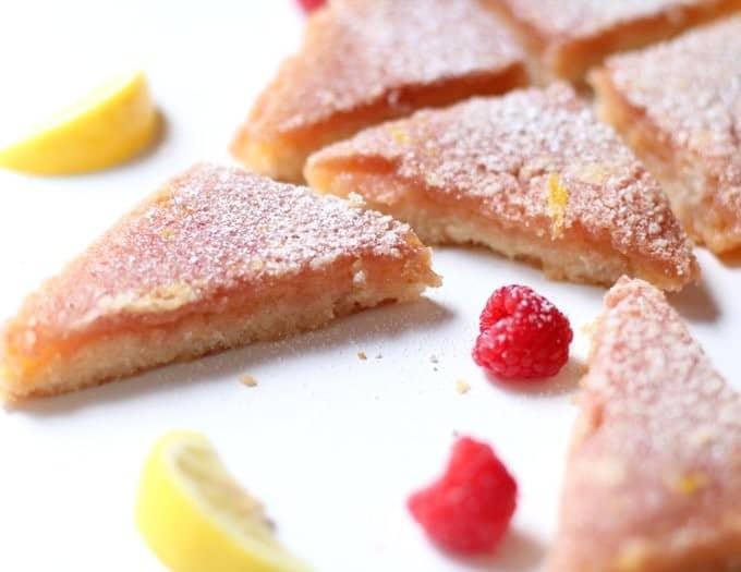 lemon bars and raspberries on a white table