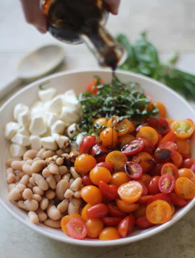 white beans, tomatoes, mozzarella and basil in a white bowl