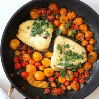 slow roasted halibut in a skillet with cherry tomatoes