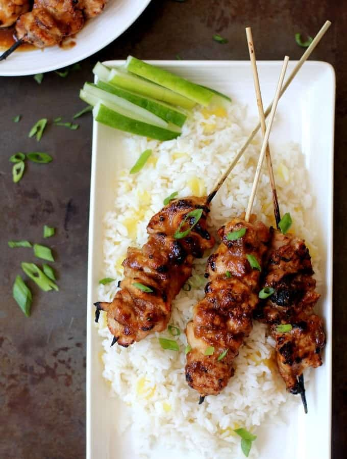 honey garlic glazed chicken skewers on a bed of pineapple rice on a white platter