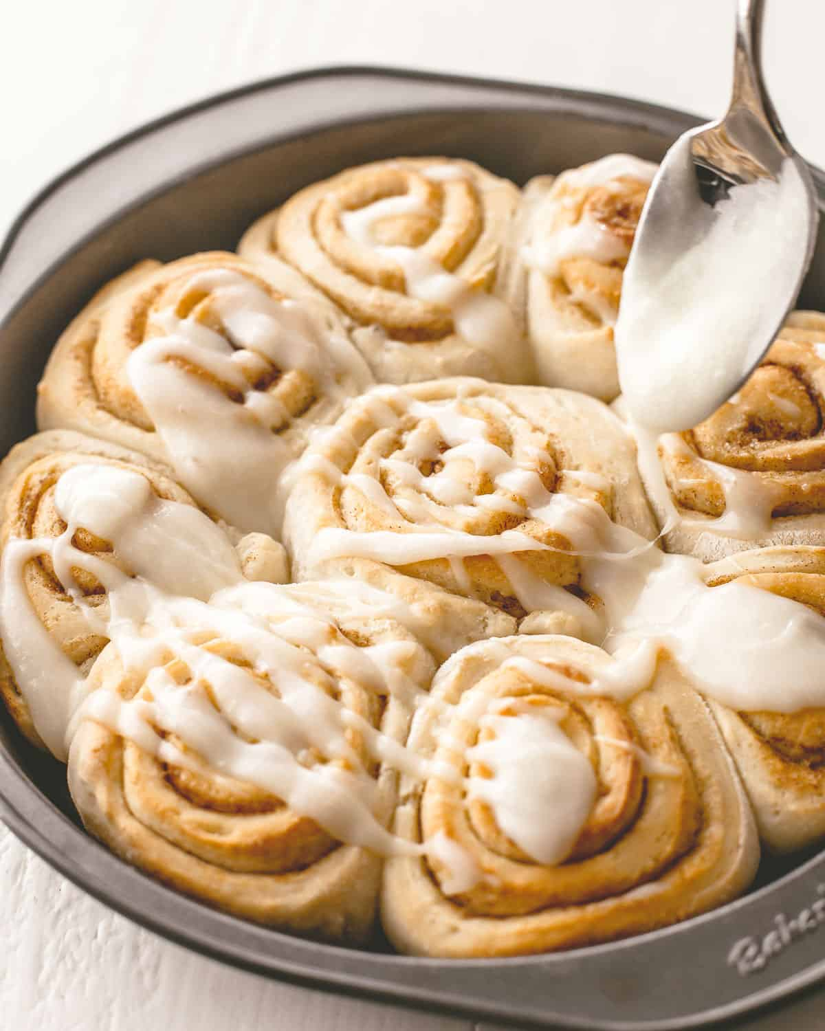 drizzling icing on top of cinnamon rolls