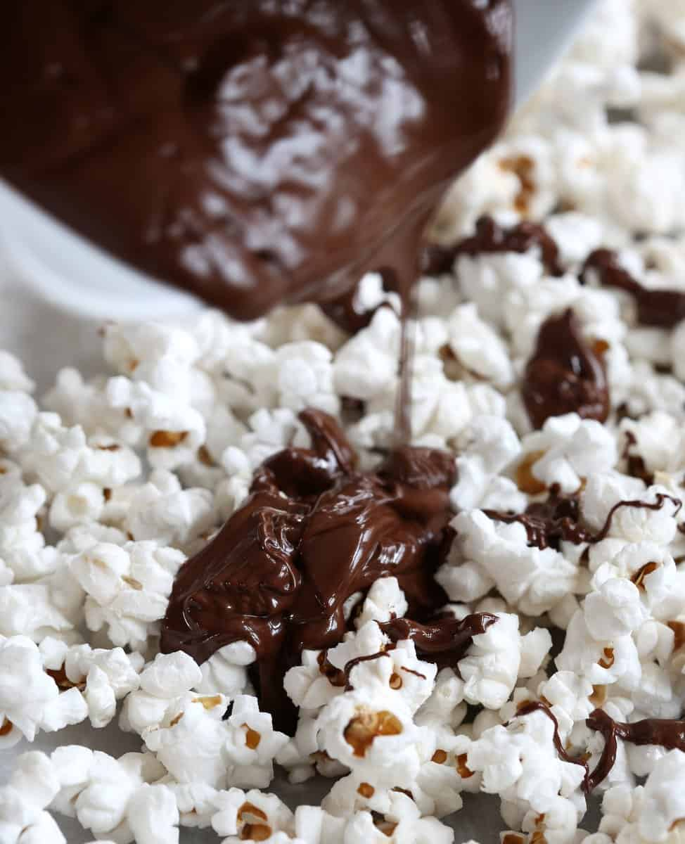 pouring chocolate over popcorn on a sheet pan