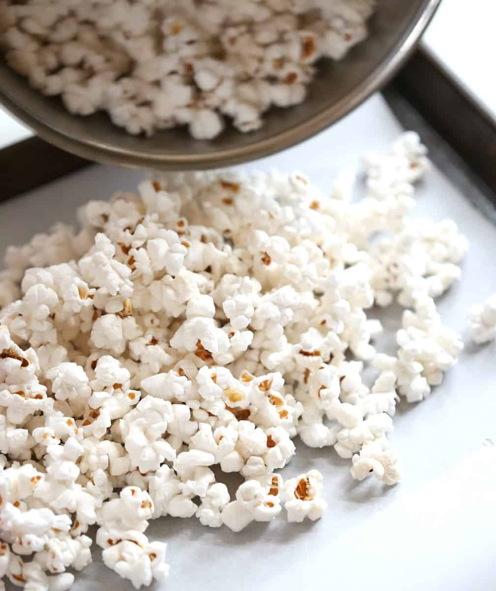 pouring popcorn on a sheet pan