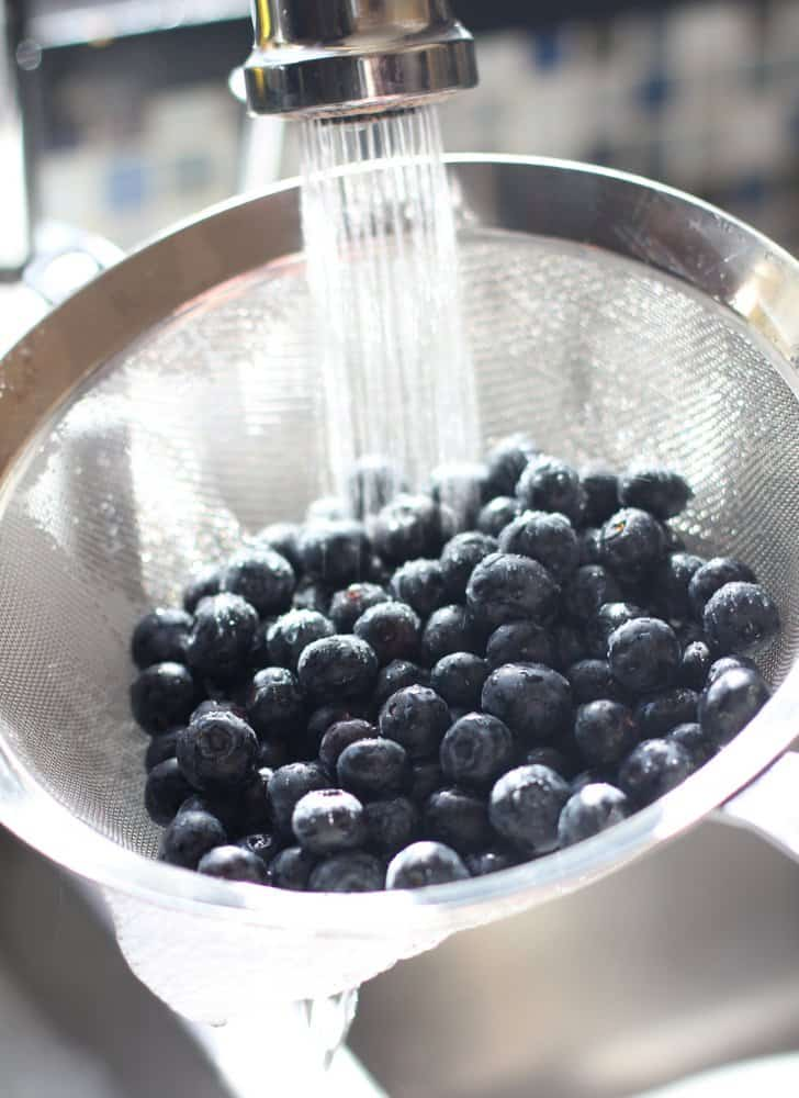 rinsing blueberries in a wire strainer