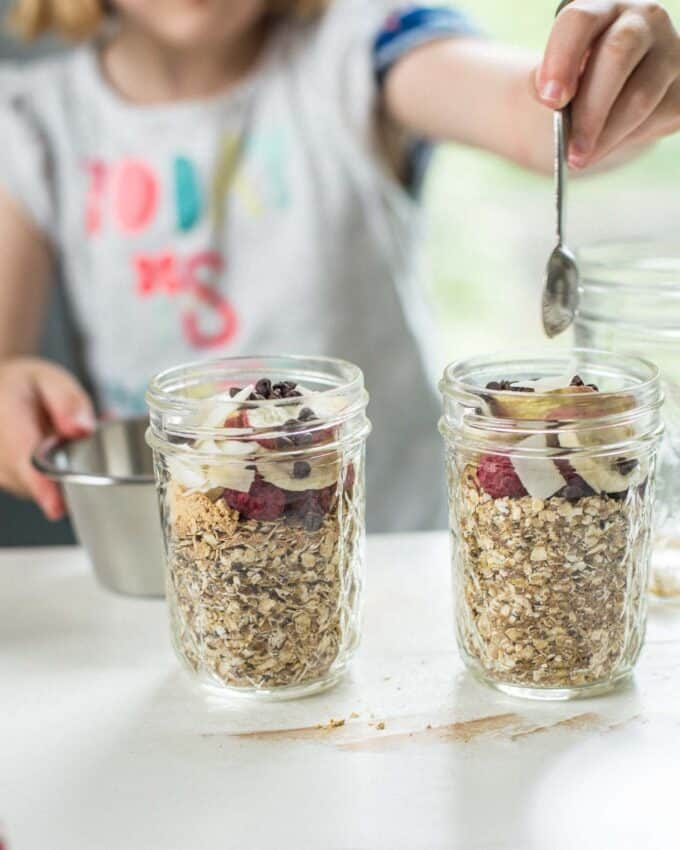 adding toppings to oatmeal in glass jars