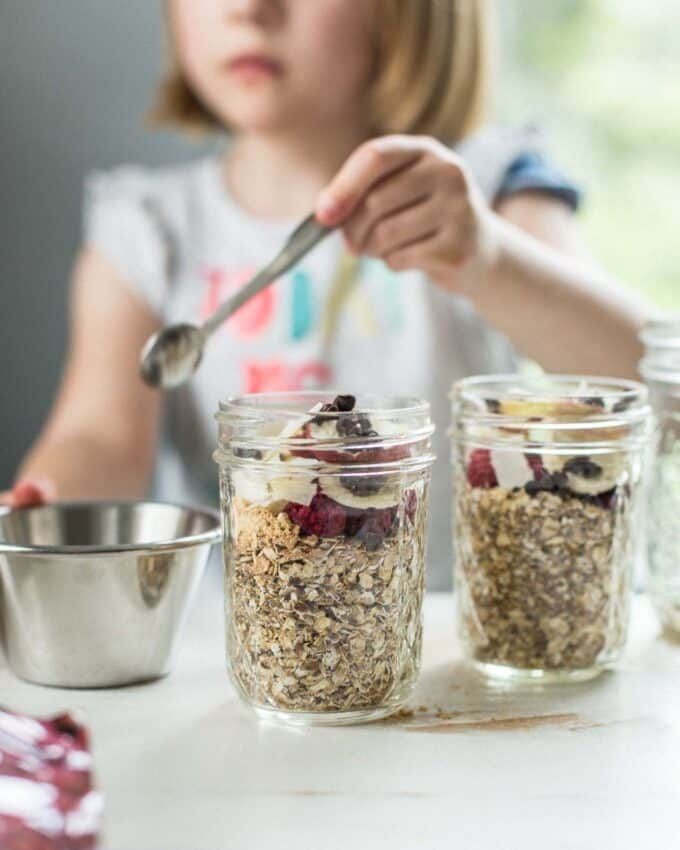 adding toppings to oatmeal in small glass jars