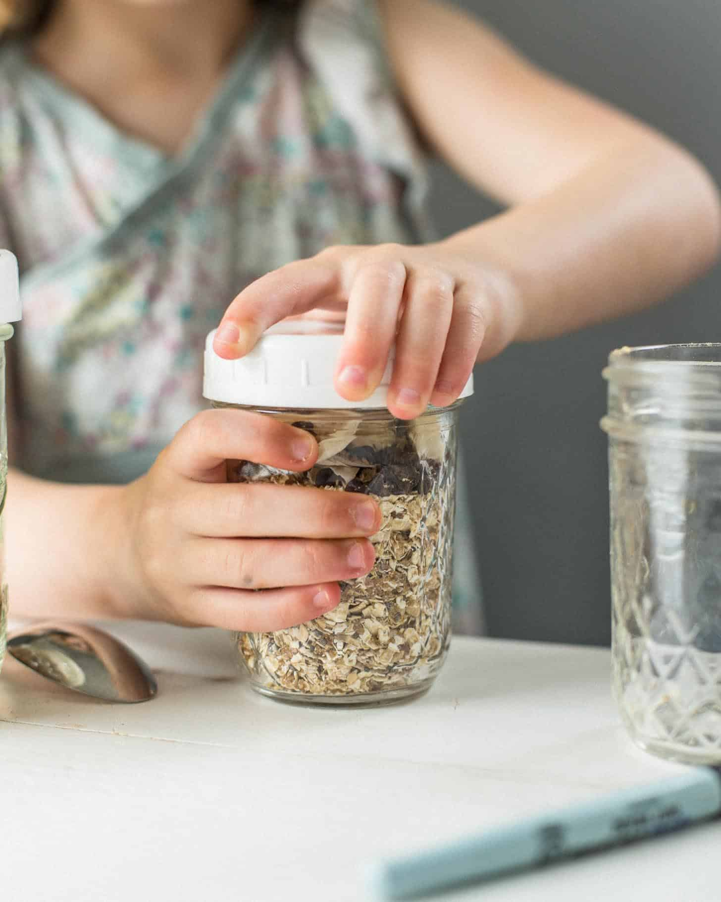 adding a top to a mason jar full of oatmeal