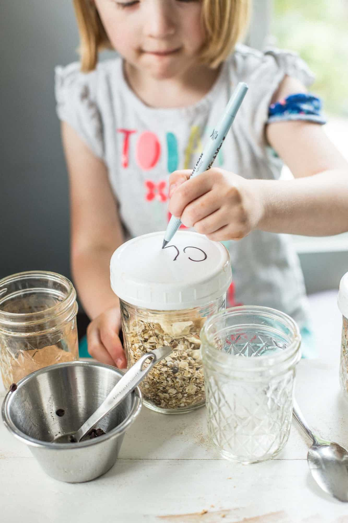 little girl writes her name on the lid of a mason jar
