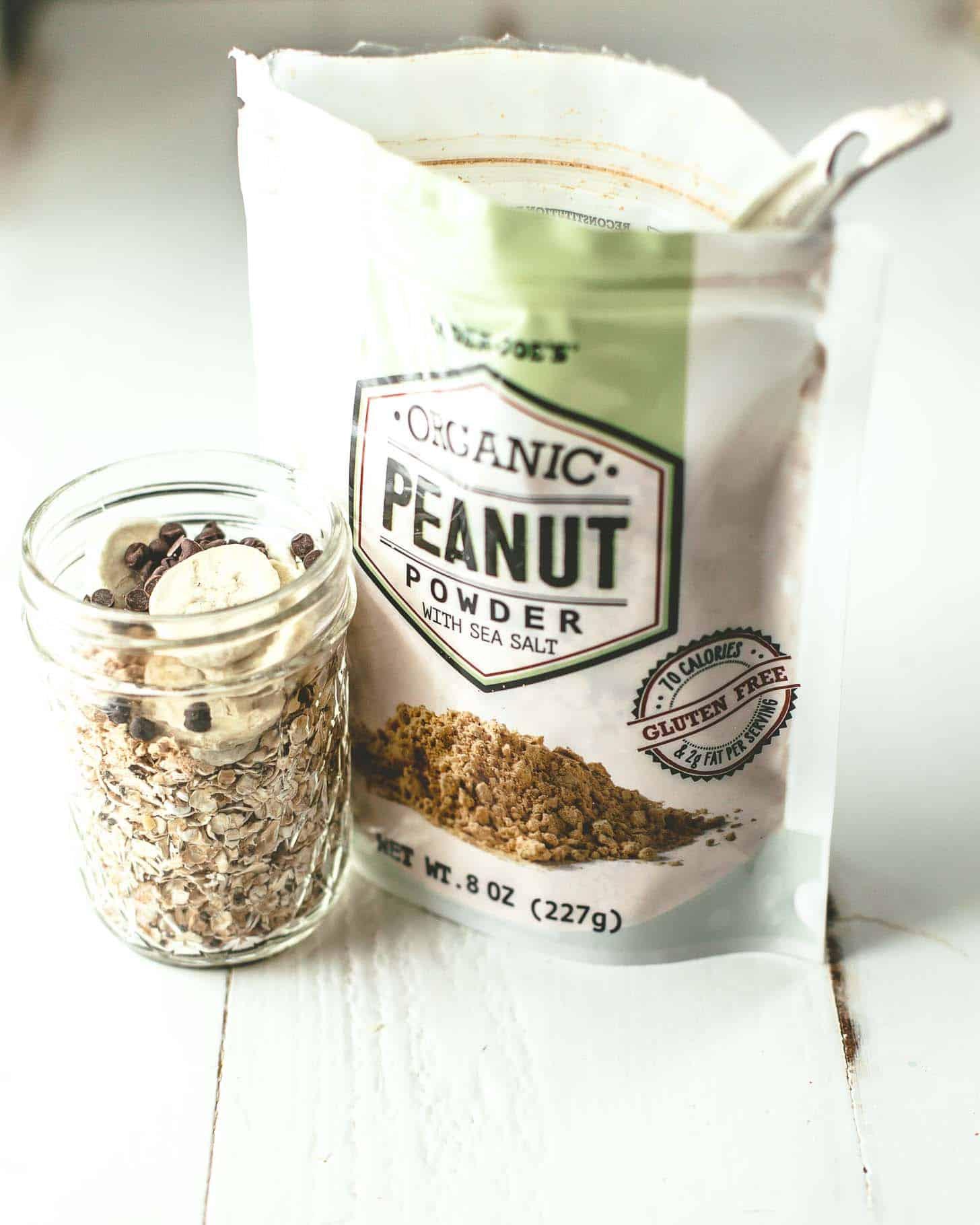 a mason jar of homemade oatmeal next to a bag of peanut powder