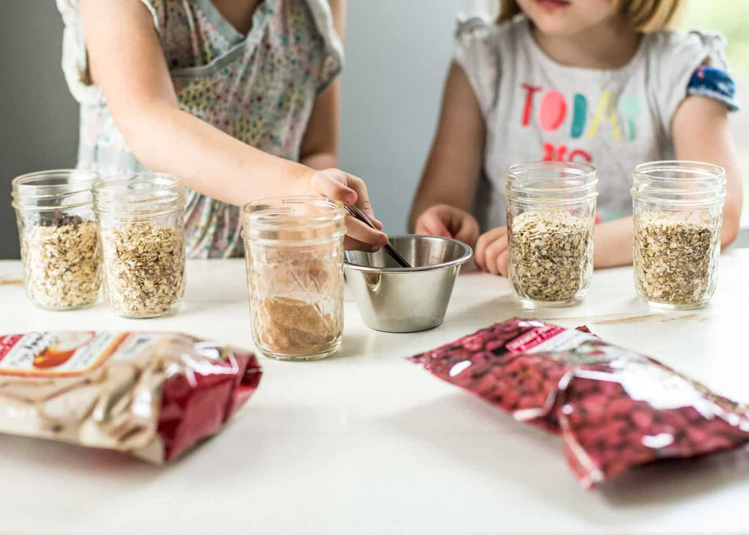 little girls add toppings to their oatmeal