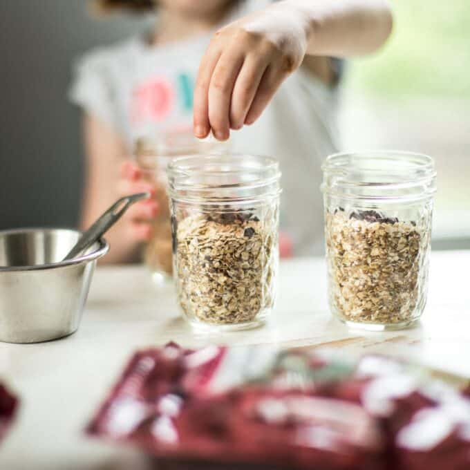 little girl adds a topping to her oatmeal