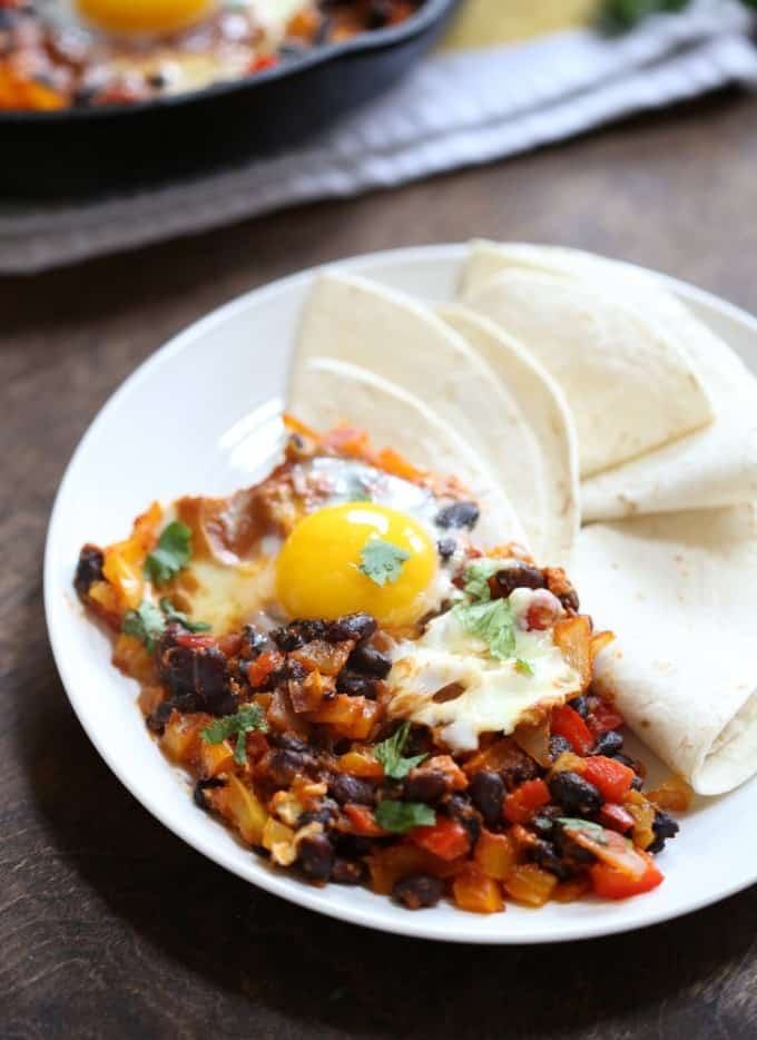huevos rancheros on a white plate with tortillas