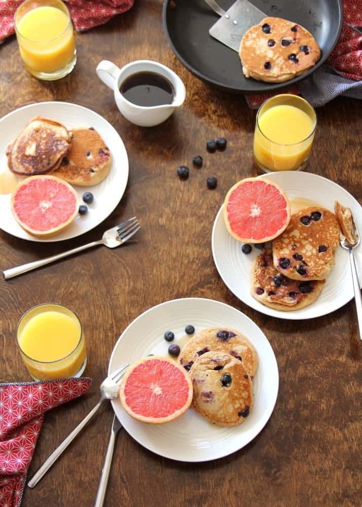 Blueberry Pancakes on white plates with grapefruit halves