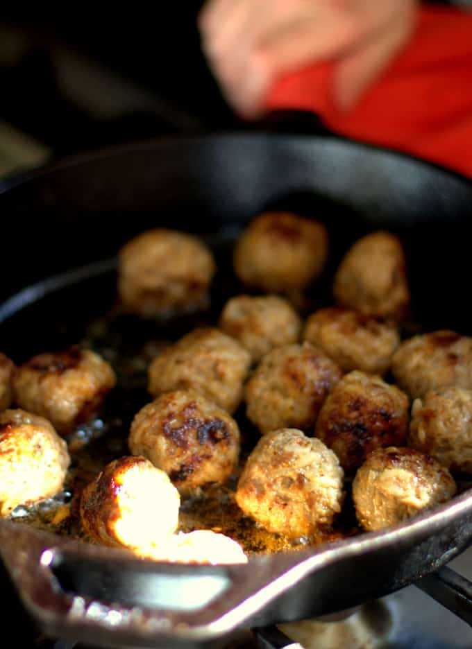 browning meatballs in a cast iron skillet