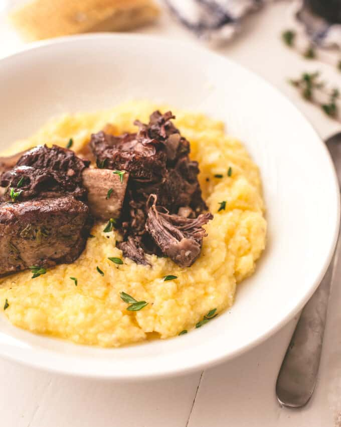 short ribs over polenta in a white bowl