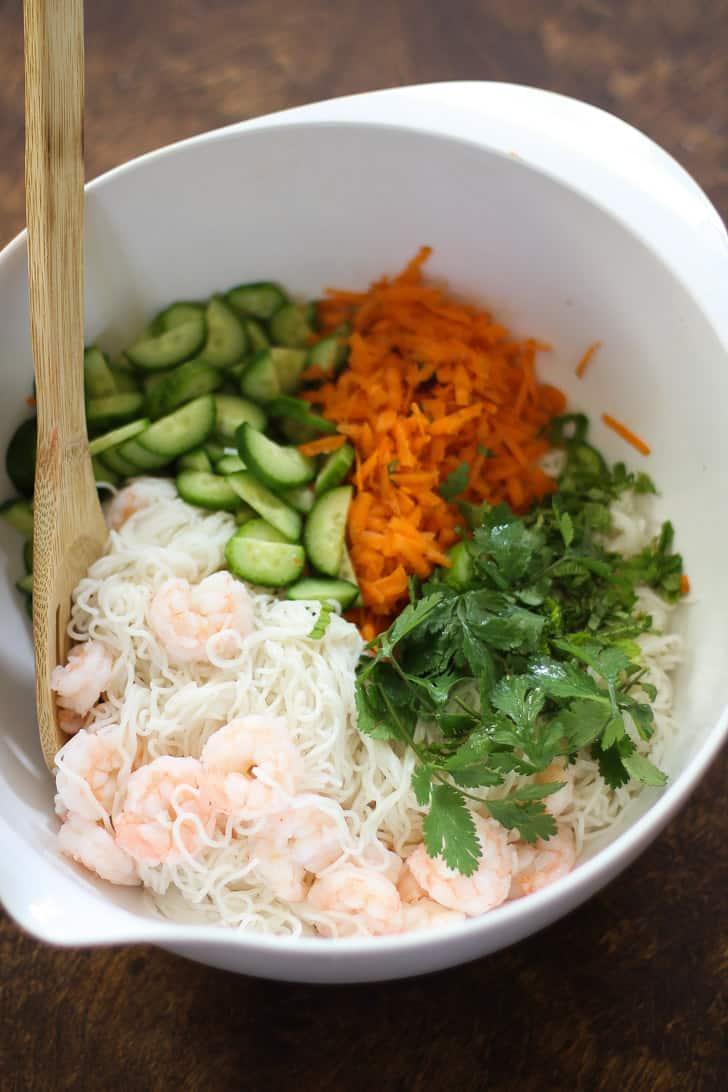 shrimp, noodles, vegetables and cilantro in a white bowl