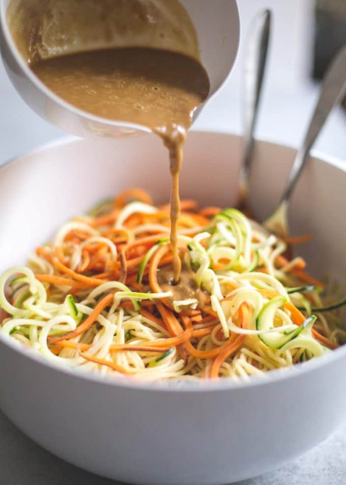 adding peanut sauce to zoodles in a white bowl