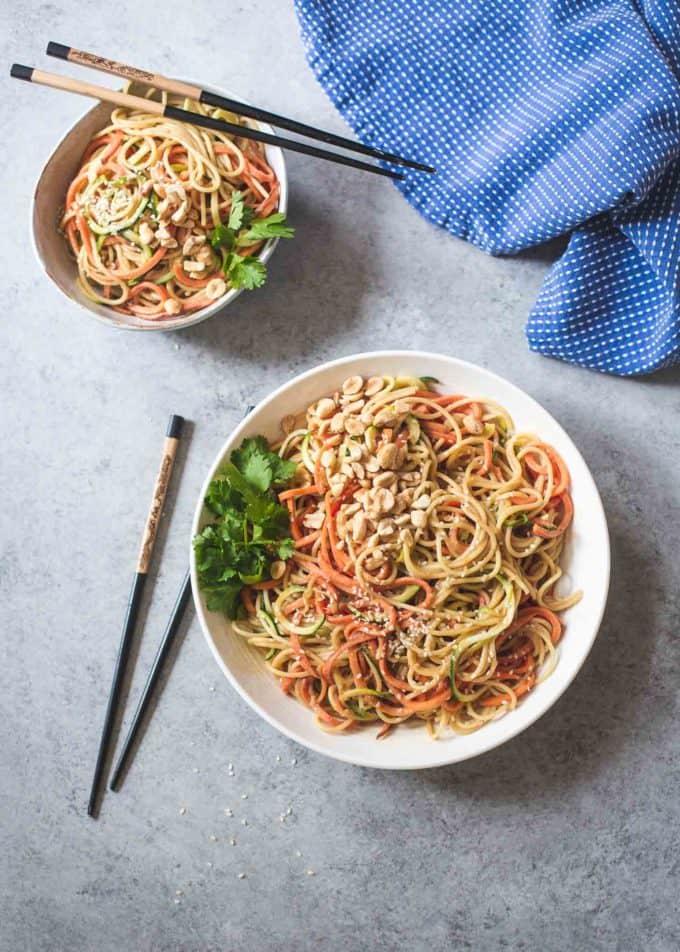Sesame Peanut Noodles in white bowls with chopsticks